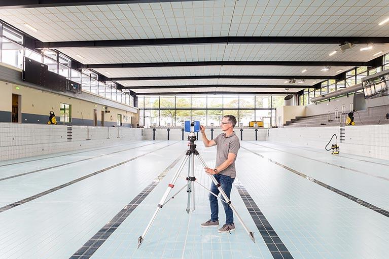 3D-Laserscanner in leerem Schwimmbecken eines Schwimmstadions